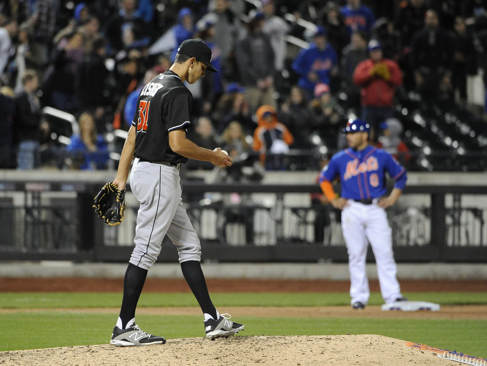 Photo - Miami Marlins relief pitcher Steve Cishek (31) reacts on the mound after giving up a double to New York Mets' Kirk Nieuwenhuis that advanced Omar Quintanilla, right, to third base in the ninth inning of a baseball game at Citi Field on Friday, April 25, 2014, in New York. 2The Mets won 4-3. (AP Photo/Kathy Kmonicek)