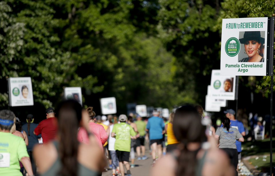 Photo - Signs honoring those lost in the 1995 bombing of the Alfred P. Murrah Federal Building line NW 41 Street as half marathoners run past them during Oklahoma City Memorial Marathon in Oklahoma City, Sunday, April 28, 2019. [Sarah Phipps/The Oklahoman]