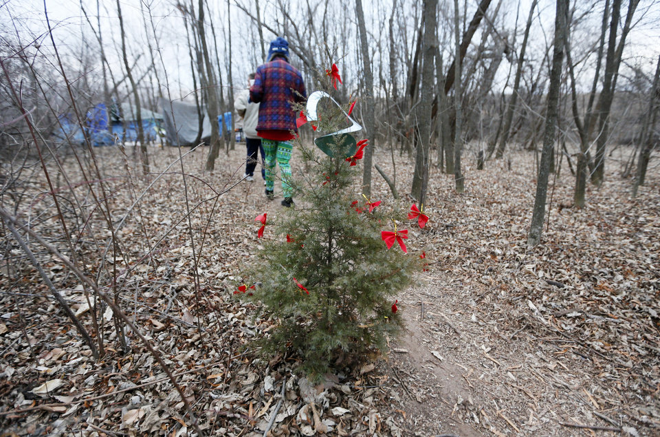 Photo -  Alyce Furr, front, and Barbara Hill pass a Christmas tree on their way into camp. [Photo by Nate Billings, The Oklahoman]