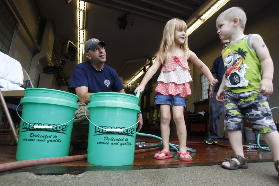 Photo - Firefighter Bryan West, left, works with Clara Cousino, 4, center, and Clay Cousino, 2, right, both to fill buckets with water at the fire station in Oregon, Ohio, Tuesday, Aug. 2, 2014. Ohio's governor is declaring a state of emergency in northwest Ohio, where about 400,000 people are being warned not to drink the water. Officials issued the warning Saturday after tests revealed the presence of a toxin possibly from algae on Lake Erie. (AP Photo/The Blade, Isaac Hale)  MANDATORY CREDIT; MAGS OUT; NO SALES; TV OUT; SENTINEL-TRIBUNE OUT; MONROE EVENING NEWS OUT; TOLEDO FREE PRESS OUT