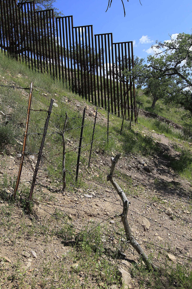 Photo - In this Friday, Aug. 10, 2012 photo, a small barbed-wire fence begins where the more imposing fence ends on the property of rancher Dan Bell, along the border between the United States and Mexico, in Nogales, Ariz. When Bell drives through his property, he speaks of the hurdles that the Border Patrol faces in his rolling green hills of oak and mesquite trees: The hours it takes to drive to some places, the wilderness areas that are generally off-limits to motorized vehicles, and the environmental reviews required to extend a dirt road. (AP Photo/Ross D. Franklin)