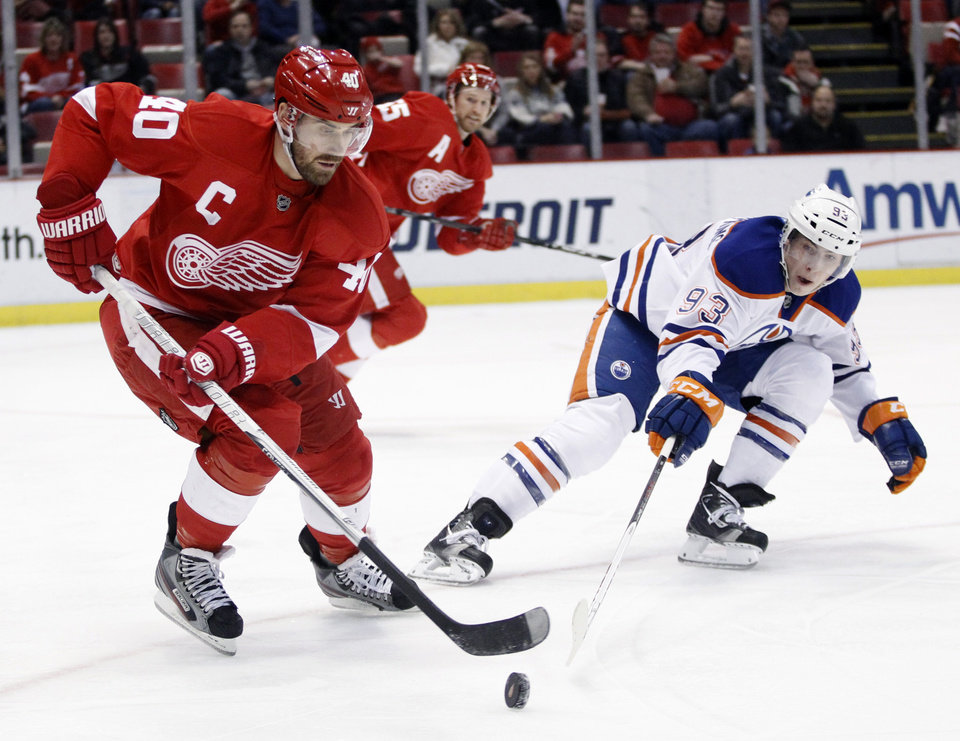 Detroit Red Wings center Henrik Zetterberg (40), of Sweden, tries to keep the puck away from Edmonton Oilers center Ryan Nugent-Hopkins (93) during the first period of an NHL hockey game Saturday, Feb. 9, 2013, in Detroit. (AP Photo/Duane Burleson)