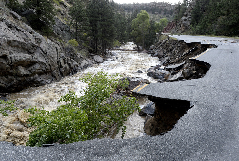 Photo - FILE- In this Sept. 14, 2013, file photo, a portion of Lefthand Canyon Road near the intersection of Olde Stage Road in Boulder, Colo., is destroyed by floodwaters. Colorado transportation officials are scrambling to replace key mountain highways with at least gravel before the first winter storms hit as early as October, but rebuilding every flood-damaged road and bridge in the mountains and plains will have to wait until 2014 _ or beyond. (AP Photo/Daily Camera, Jeremy Papasso, File)