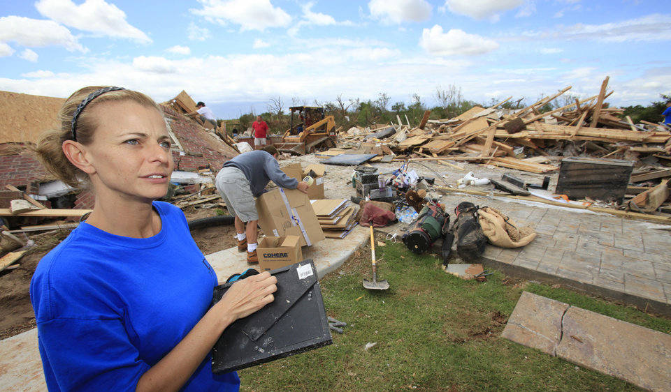 Tornado aftermath cleanup east of Piedmont, Wednesday, May 25, 2011. Tiffany Johnson clasps a photo retrieved from the rubble of her home that was hit by the tornado Tuesday evening. Photo by David McDaniel, The Oklahoman