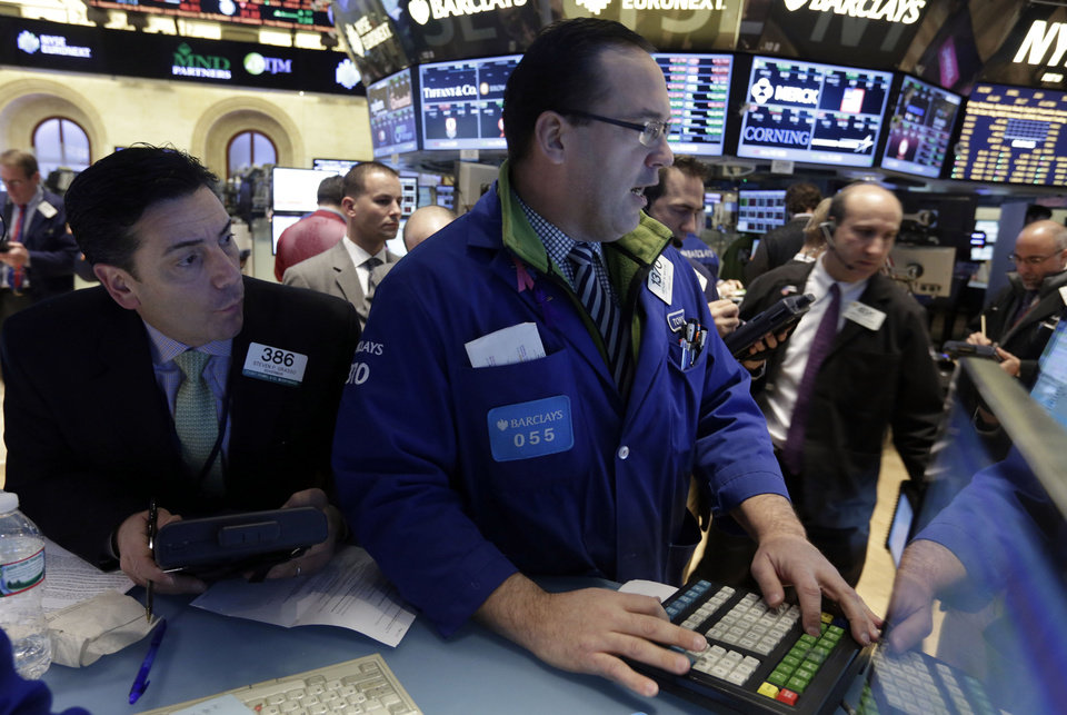 Photo - Trader Steven Grasso, left, looks over the shoulder of specialist  Anthony Matesic on the floor of the New York Stock Exchange Tuesday, Feb. 4, 2014. Stocks are mixed on Wall Street after suffering big losses the day before. (AP Photo/Richard Drew)