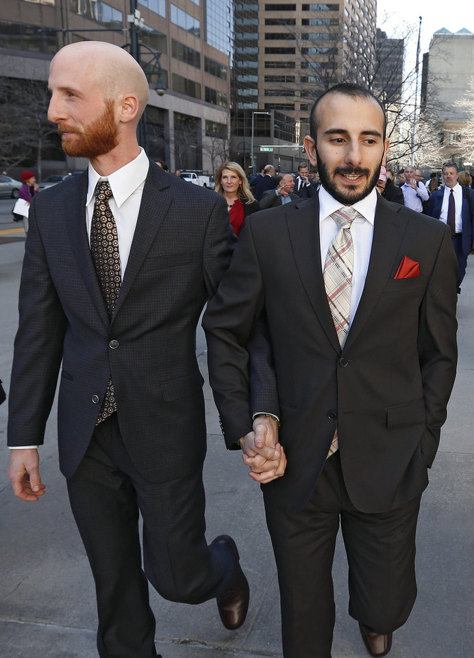 Photo - Plaintiffs challenging Utah's gay marriage ban Moudi Sbeity, right, and his partner Derek Kitchen, hold hands as they leave the courthouse following a hearing at the U.S. Circuit Court of Appeals in Denver, Thursday, April 10, 2014. The court is to decide if it agrees with a federal judge in Utah who in mid-December overturned a 2004 voter-passed gay marriage ban, saying it violates gay and lesbian couples' rights to due process and equal protection under the 14th Amendment. (AP Photo/Brennan Linsley)