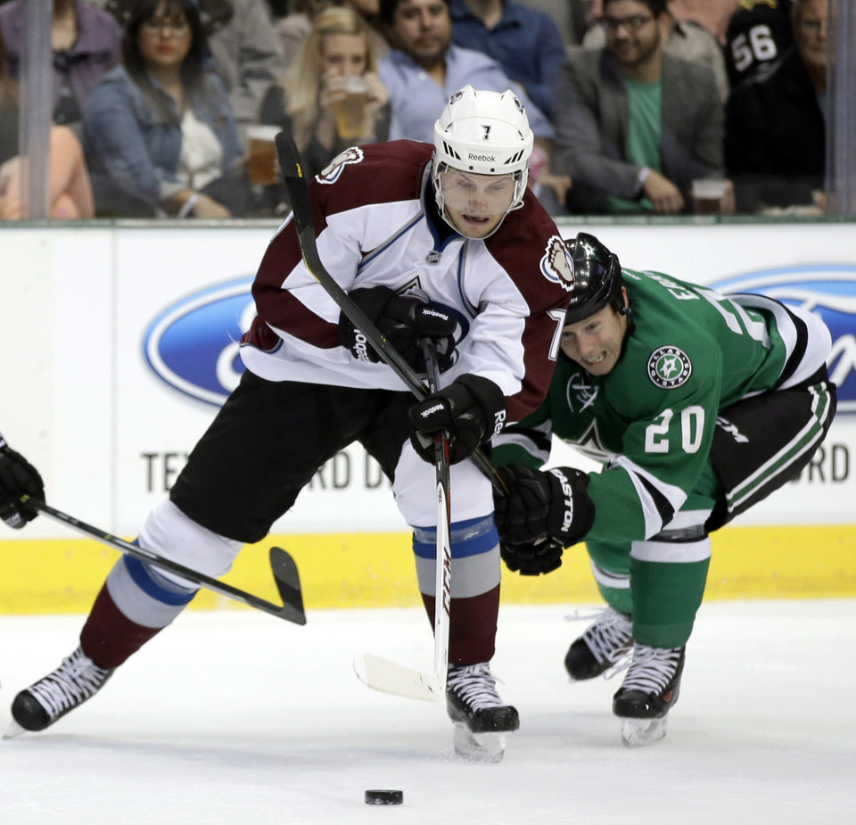 Photo - Colorado Avalanche center John Mitchell (7) and Dallas Stars center Cody Eakin (20) compete for control of a loose puck in the first period of a preseason NHL hockey game on Thursday, Sept. 26, 2013, in Dallas. (AP Photo/Tony Gutierrez)