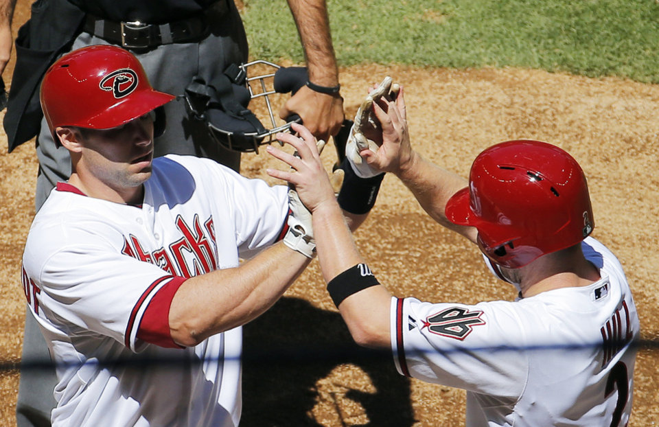 Arizona Diamondbacks' Paul Goldschmidt, left, high fives teammate Aaron Hill after hitting a two-run home run against the San Francisco Giants during the first inning of a baseball game, Thursday, April 3, 2014, in Phoenix. (AP Photo/Matt York)
