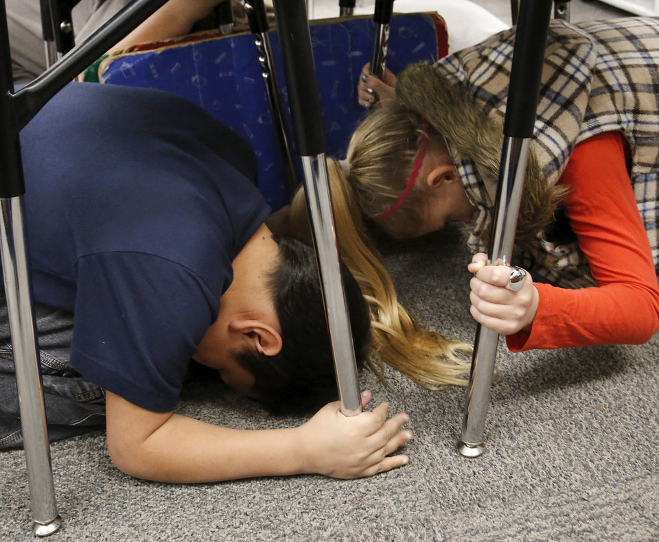 "Students take cover under their desks in Melinda Jordan's fourth grade classroom.  Cleveland Bailey Elementary School students participated in the ""Drop, Cover and Hold-on"" multi-state earthquake drill at the Midwest City school Wednesday,  Feb. 7,  2013.    Photo by Jim Beckel, The Oklahoman"