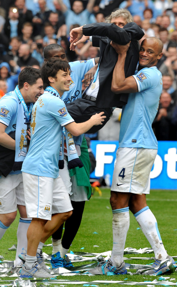 Photo - Manchester City's manager Manuel Pellegrini is carried by Vincent Kompany, right, David Silva, center left, Samir Nasri, left, and Yaya Toure after Manchester City are crowned Premier League Champions  after the English Premier League soccer match between Manchester City and West Ham United at the Etihad Stadium,  Manchester, England, Sunday, May 11, 2014. (AP Photo/Rui Vieira)