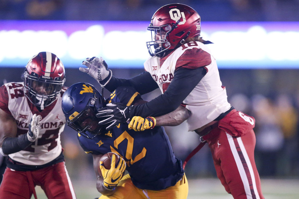 Photo - Oklahoma Sooners linebacker Curtis Bolton (18) pushed West Virginia Mountaineers wide receiver Gary Jennings Jr. (12) out of bounds during the NCAA football game between the Oklahoma Sooners and the West Virginia Mountaineers at Mountaineer Field at Milan Puskar Stadium in Morgantown, W.Va on Friday, November 23, 2018. IAN MAULE/Tulsa World