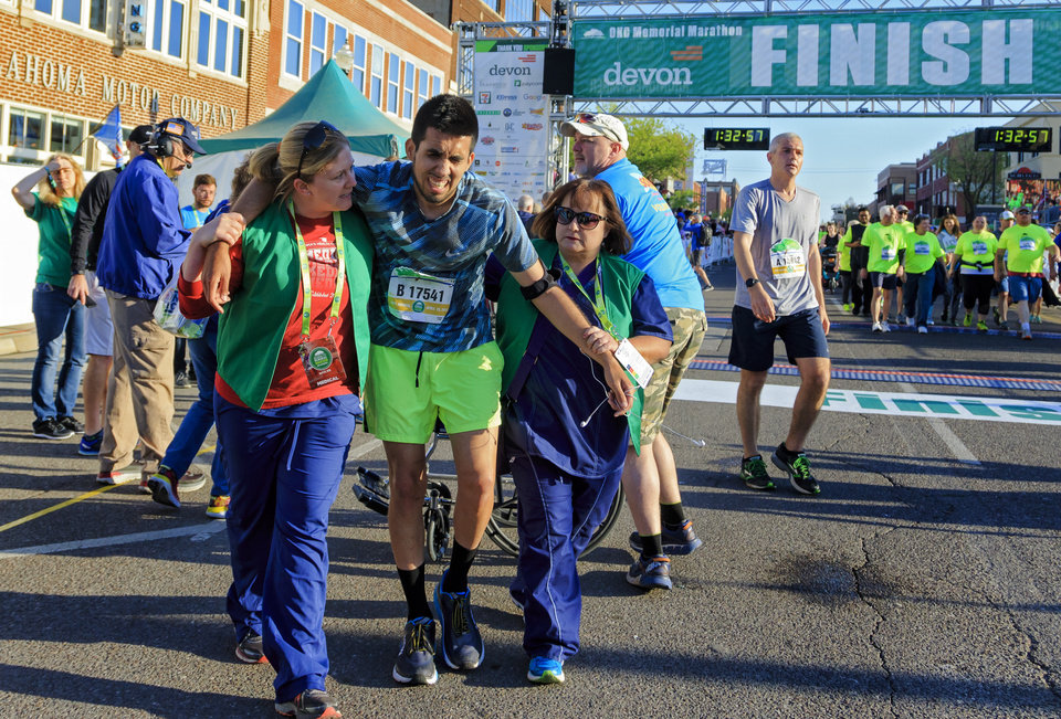 Photo - Pedro Becerra has assistance after finishing the half marathon during the Oklahoma City Marathon in Oklahoma City, Okla. on Sunday, April 29, 2018.  . Photo by Chris Landsberger, The Oklahoman