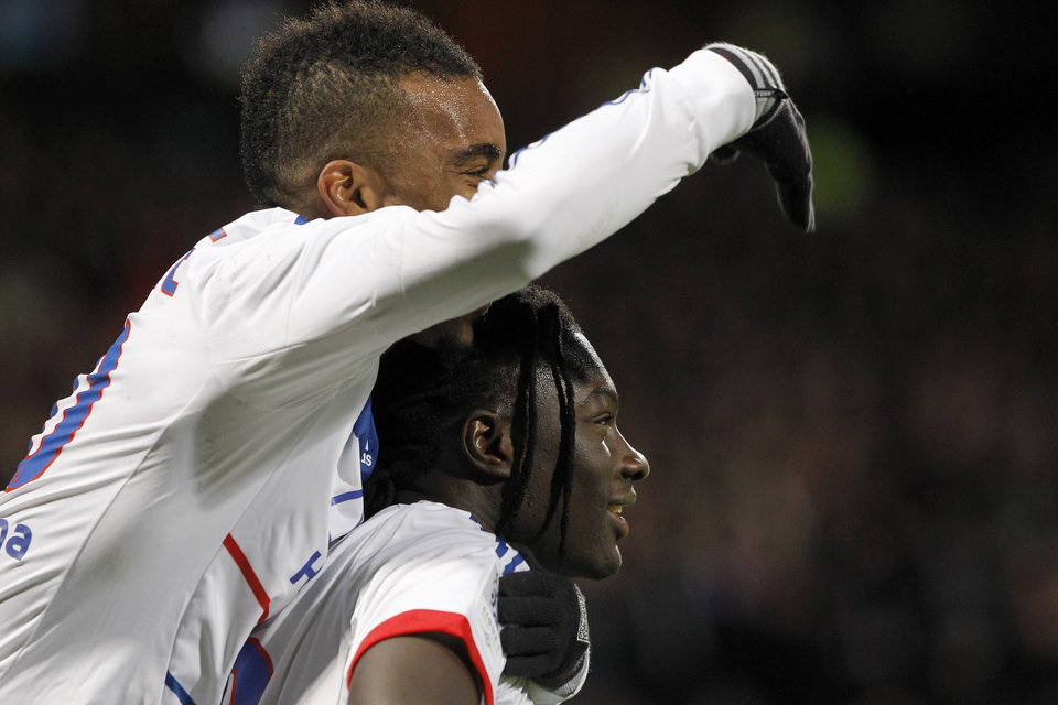 Photo - Lyon's Bafe Gomis, down, celebrates with Alexandre Lacazette, up, after he scored a goal against Montpellier during their French League One soccer match at Gerland stadium, in Lyon, central France, Saturday, Dec. 1, 2012. (AP Photo/Laurent Cipriani)