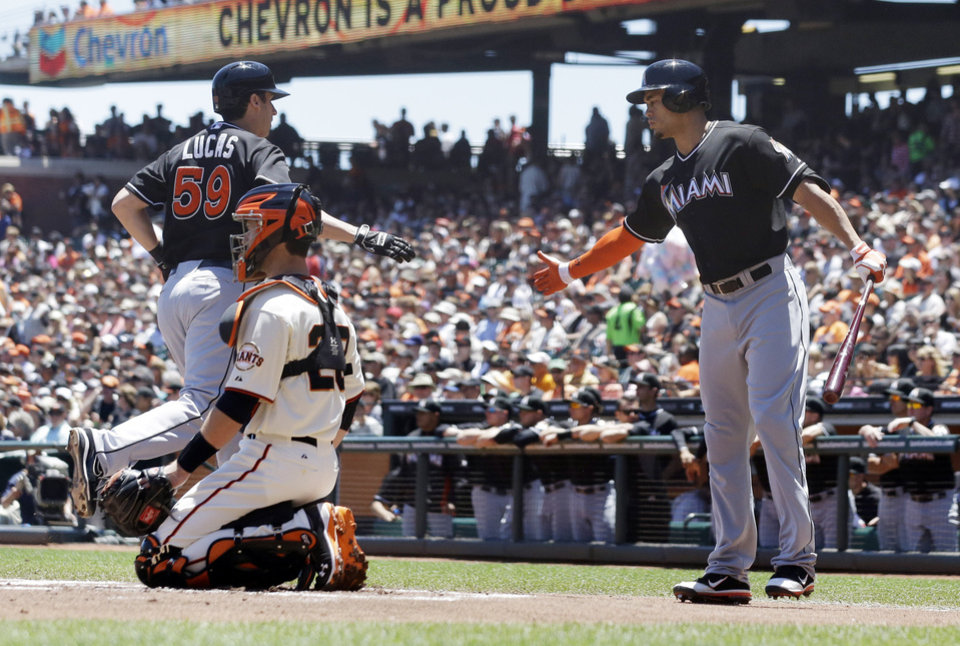 Photo - Miami Marlins' Ed Lucas, left, celebrates his solo home run with teamate Giancarlo Stanton during the first inning of a baseball game against the San Francisco Giants on Saturday, June 22, 2013, in San Francisco. (AP Photo/Marcio Jose Sanchez)