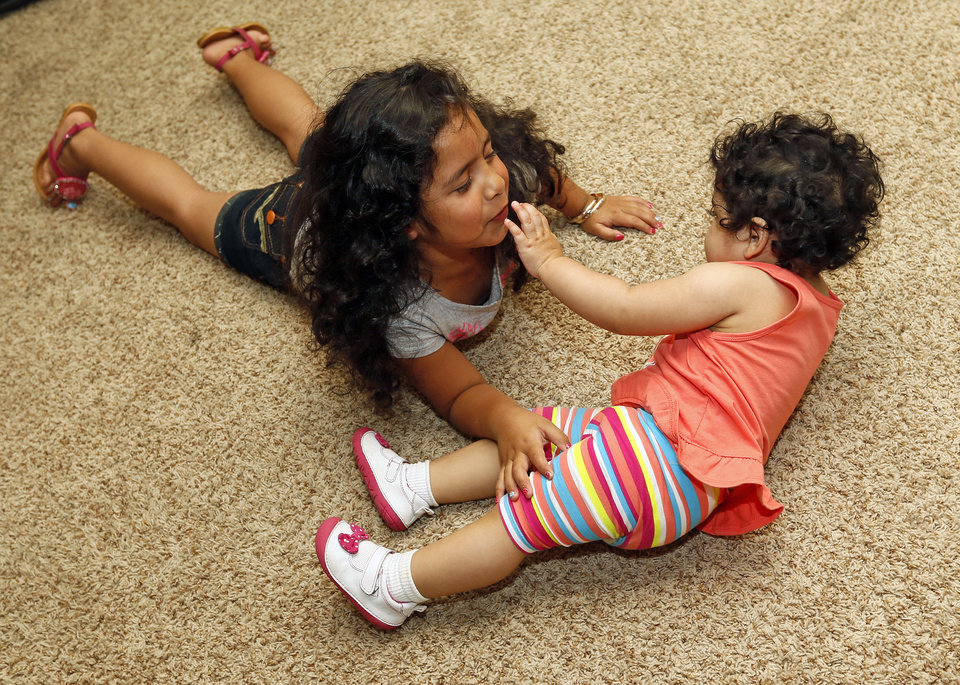 Photo - Kaylee Sanchez, 6, plays with her sister Ellie Sanchez, 1, at their home in the Plaza Towers neighborhood in Moore. Photo by Nate Billings, The Oklahoman   NATE BILLINGS - NATE BILLINGS