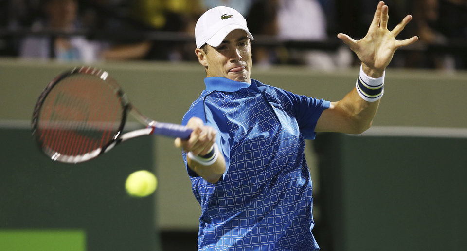 Photo - John Isner, of the United States, returns the ball to Nicolas  Almagro, of Spain, during the Sony Open Tennis in Key Biscayne, Fla., Monday, March 24, 2014. (AP Photo/J Pat Carter)