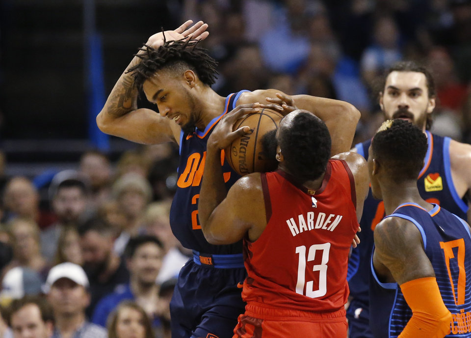 Photo - Oklahoma City Thunder guard Terrance Ferguson, left, collides with Houston Rockets guard James Harden (13) during the second half of the team's NBA basketball game Tuesday, April 9, 2019, in Oklahoma City. (AP Photo/Sue Ogrocki)