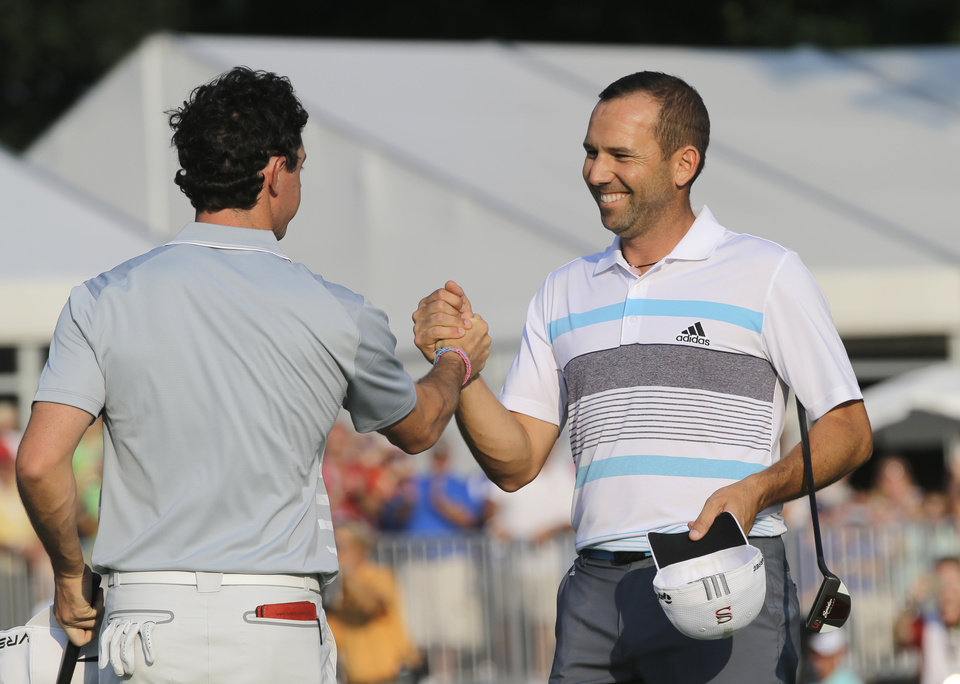 Photo - Sergio Garcia, right, congratulates Rory McIlroy after the final round of the Bridgestone Invitational golf tournament Sunday, Aug. 3, 2014, at Firestone Country Club in Akron, Ohio. McIlroy beat Garcia by two shots for the championship. (AP Photo/Mark Duncan)