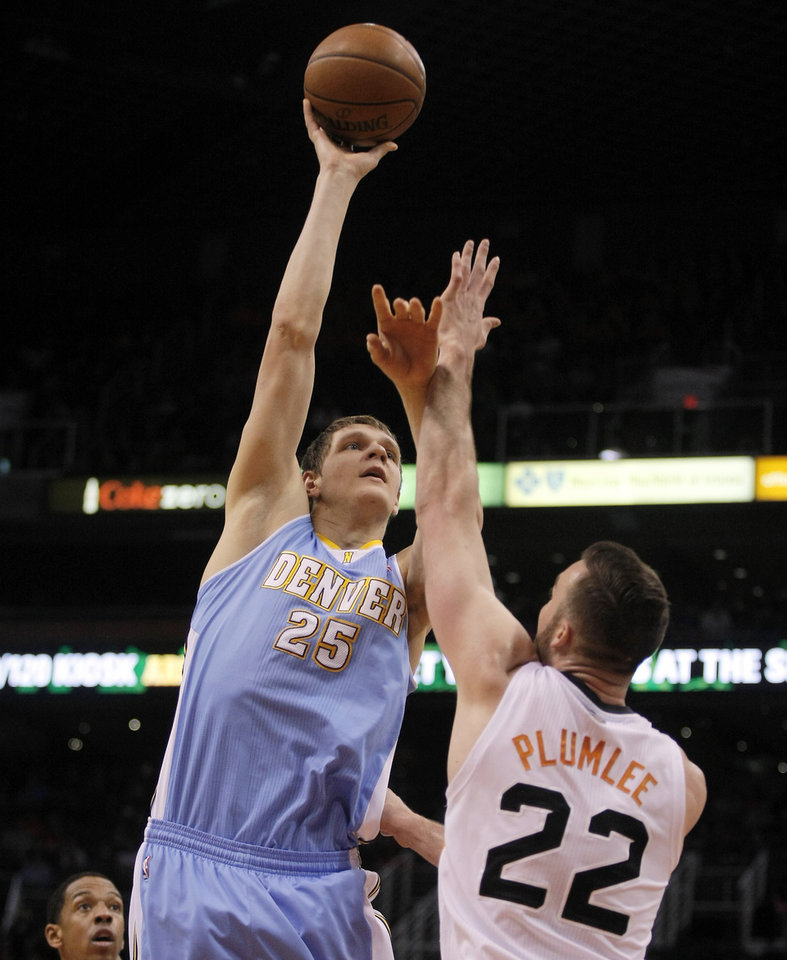 Photo - Denver Nuggets center Timofey Mozgov (25) shoots over Phoenix Suns center Miles Plumlee (22) in the second quarter during an NBA basketball game, Sunday, Jan. 19, 2014, in Phoenix. (AP Photo/Rick Scuteri)