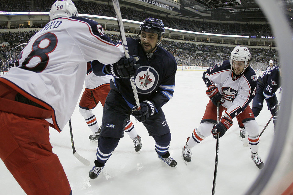Photo - Winnipeg Jets' Dustin Byfuglien (33) fights for position against Columbus Blue Jackets' David Savard (58) and Artem Anisimov (42) during second period of an NHL hockey game in Winnipeg, Manitoba, on Saturday, Jan. 11, 2014. (AP Photo/The Canadian Press, John Woods)