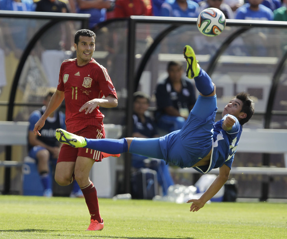 Photo - El Salvador's Alexander Larin (13) makes on overhead kick as Spain's Pedro Rodriguez (11) defends during the first half of an exhibition soccer game, Saturday, June 7, 2014, in Landover, Md. (AP Photo/Luis M. Alvarez)