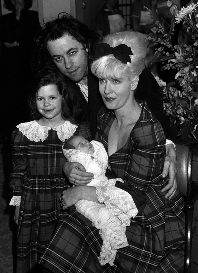Photo - FILE - In this March 16, 1989 file photo rock star Bob Geldof, his wife, TV presenter Paula Yates, right, and their five-year-old daughter Fifi Trixiebelle, left, show off the new addition to their family, an as yet unnamed baby girl, later named Peaches, at St Mary's Hospital in Paddington, London. Peaches Geldof, the model and television presenter who was concert organizer Bob Geldof's daughter, has died at age 25. Bob Geldof said in a statement Monday, April 7, 2014: