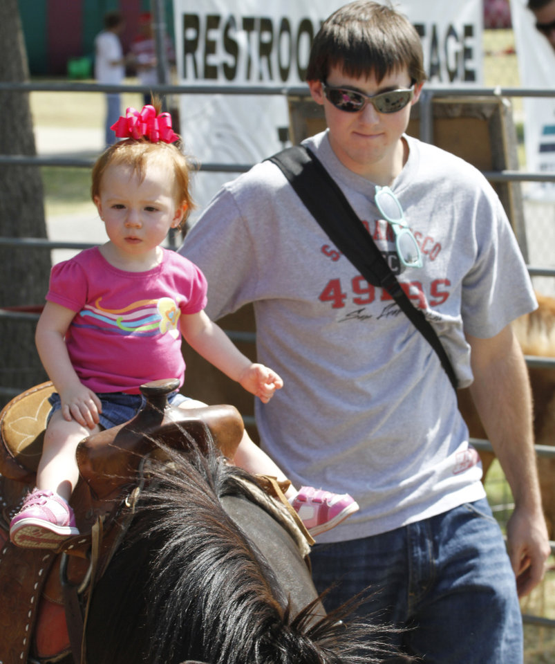 Ryan Morgan helps his 1-year-old daughter, Leila, ride a pony during Freedom Festival at Eldon Lyon Park in Bethany, Wednesday, July 4, 2012. Photo By Steve Gooch, The Oklahoman