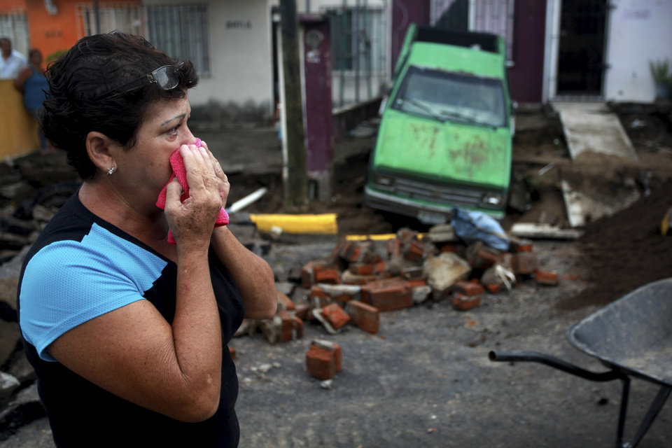 Photo - Maria del Carmen Gonzalez watches after part of a street and her home collapsed due to heavy rains in the Gulf port city of Veracruz, Mexico, Tuesday Sept. 2, 2014. The Gulf states of Mexico are bracing for more bad weather as Tropical Storm Dolly will cross the coast lat this evening or overnight and continue moving inland over northeastern Mexico on Wednesday. (AP Photo/Felix Marquez)