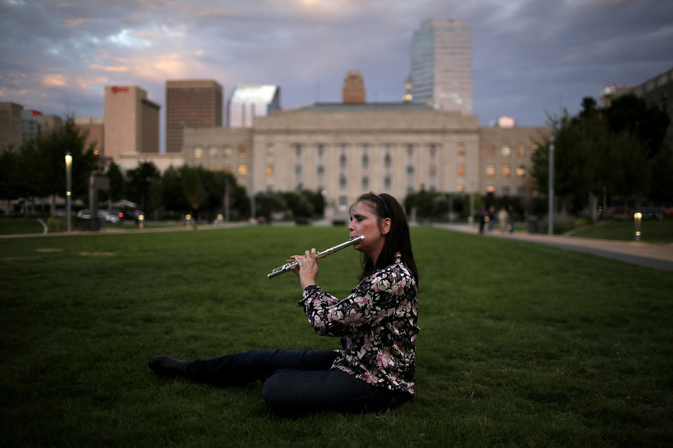 Photo - Laura Miller, of Wagoner, plays flute during a protest of a Black Mass at the Civic Center Music Hall, Sunday, Sept. 21, 2014.  Photo by Garett Fisbeck, For The Oklahoman