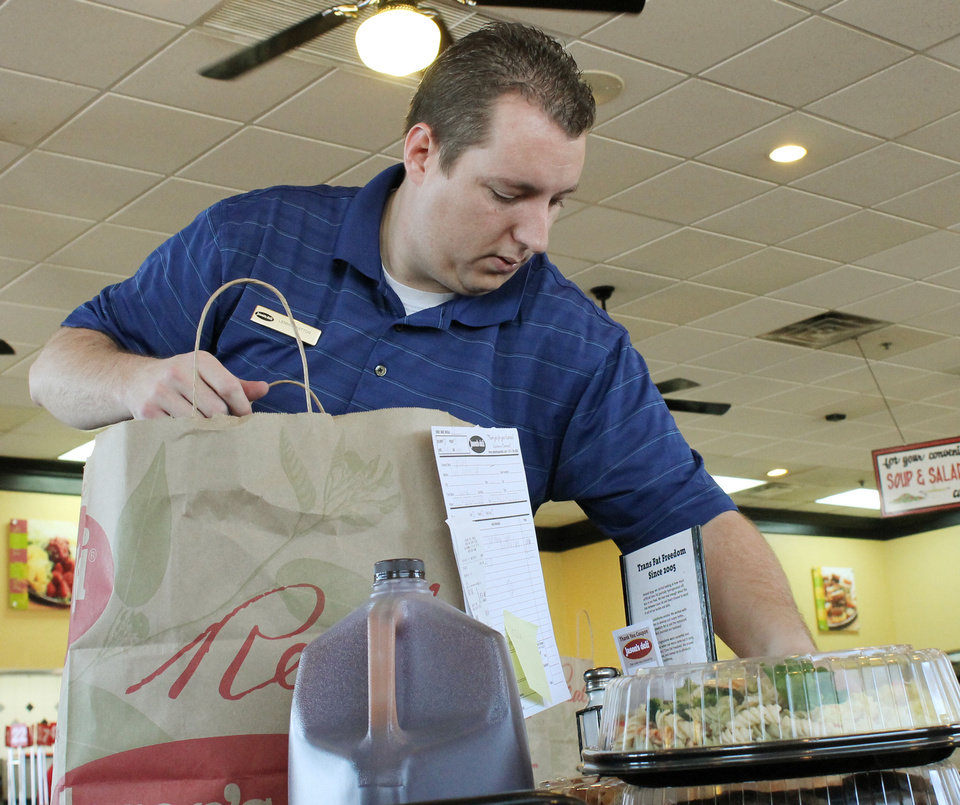 Photo - Above: Lennon Patton, director of catering sales for Jason's Deli, checks orders Thursday in Oklahoma City.