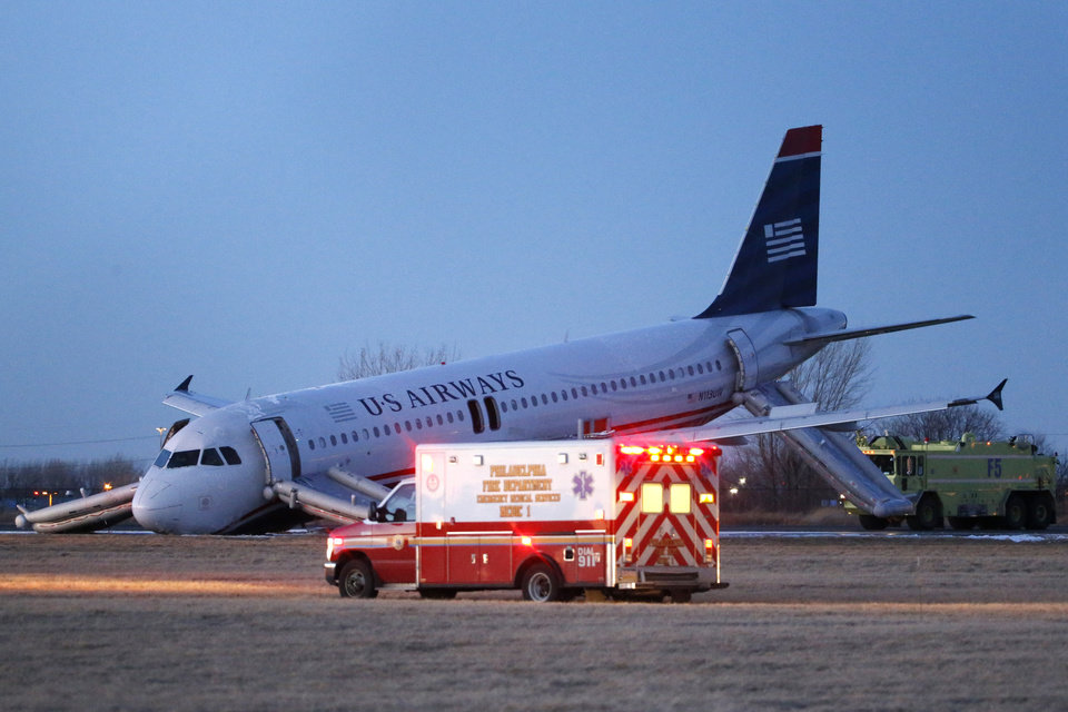 Photo - Emergency vehicles drive past a damaged US Airways jet at the end of a runway at the Philadelphia International Airport, Thursday, March 13, 2014, in Philadelphia. Airline officials said the flight was heading to Fort Lauderdale, Fla., when the pilot was forced to abort takeoff around 6:30 p.m., after the front landing gear failed. An airport spokeswoman said no injuries have been reported. (AP Photo/Matt Slocum)