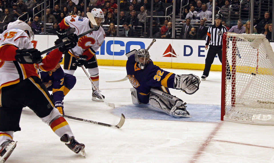 Photo - Calgary Flames left winger Mike Cammalleri (13) shoots and scores on Los Angeles Kings goalie Jonathan Quick (32) in the first period of an NHL hockey game in Los Angeles Saturday, March 9, 2013. (AP Photo/Reed Saxon)