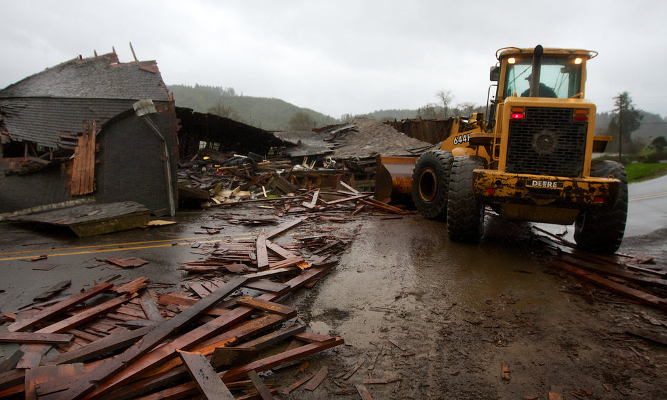 A front-end loader cleans up debris from Gary Petty's 1930-vintage barn, which collapsed across the Kilchis River Road, east of Highway 101 near Tillamook, Ore., after high high winds hit the Oregon coast on Monday, Nov. 19, 2012. (AP Photo/The Oregonian, Randy L. Rasmussen)