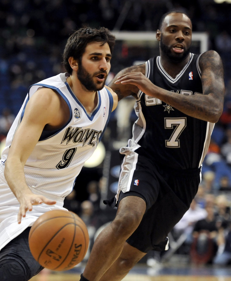 Photo - Minnesota Timberwolves' Ricky Rubio (9), from Spain, drives against San Antonio Spurs' Damion James (7) during the fourth quarter in an NBA basketball game at the Target Center on in Minneapolis on Tuesday, April 8, 2014. Timberwolves won 110-91. (AP Photo/Hannah Foslien)