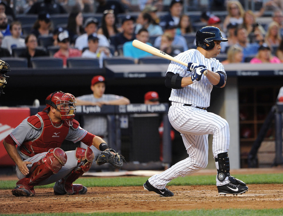 Photo - New York Yankees designated hitter Carlos Beltran follows through on an RBI single off Cincinnati Reds starting pitcher Mike Leake as Devin Mesoraco catches for the Reds in the third inning of an interleague baseball game at Yankee Stadium on Friday, July 18, 2014, in New York. (AP Photo/Kathy Kmonicek)
