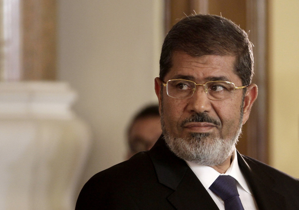 "FILE - In this Friday, July 13, 2012 file photo, Egyptian President Mohammed Morsi holds a joint news conference with Tunisian President Moncef Marzouki, unseen, at the Presidential palace in Cairo, Egypt. A statement on the Egyptian president's office's Twitter account has quoted Mohammed Morsi as calling military measures ""a full coup."" The denouncement was posted shortly after the Egyptian military announced it was ousting Morsi, who was Egypt's first freely elected leader but drew ire with his Islamist leanings. The military says it has replaced him with the chief justice of the Supreme constitutional Court, called for early presidential election and suspended the Islamist-backed constitution. (AP Photo/Maya Alleruzzo, File)"