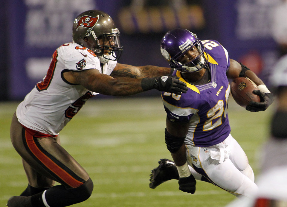 Photo -   Minnesota Vikings running back Adrian Peterson, right, runs from Tampa Bay Buccaneers middle linebacker Mason Foster during the first half of an NFL football game Thursday, Oct. 25, 2012, in Minneapolis. (AP Photo/Andy King)