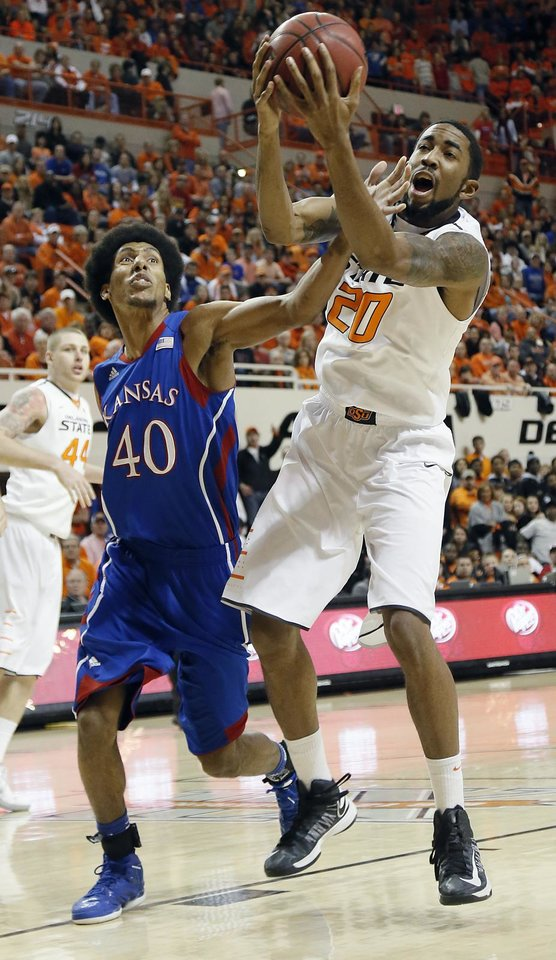 Photo - Oklahoma State 's Michael Cobbins (20) and Kansas' Kevin Young (40) battle for a rebound during the college basketball game between the Oklahoma State University Cowboys (OSU) and the University of Kanas Jayhawks (KU) at Gallagher-Iba Arena on Wednesday, Feb. 20, 2013, in Stillwater, Okla. Photo by Chris Landsberger, The Oklahoman