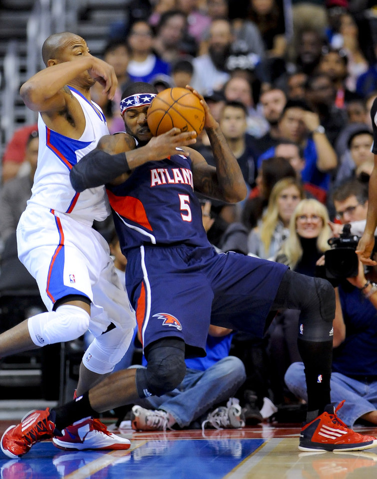 Atlanta Hawks forward Josh Smith (5) battles Los Angeles Clippers forward Caron Butler, left, while driving to the basket in the first half of an NBA basketball game on Sunday, Nov. 11, 2012, in Los Angeles. (AP Photo/Gus Ruelas)
