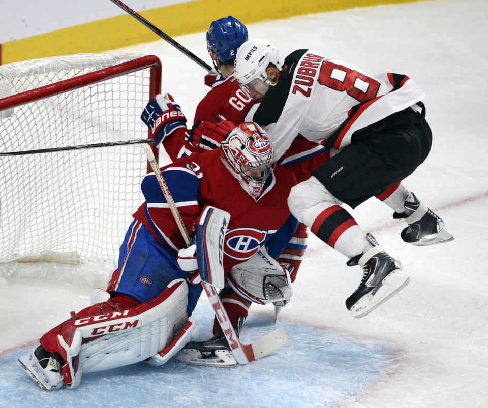 Photo - New Jersey Devils right wing Dainius Zubrus (8) jumps in front of Montreal Canadiens goalie Carey Price (31) and Montreal Canadiens defenseman Josh Gorges (26) during second period National Hockey League action, Tuesday, Jan. 14, 2014, in Montreal. (AP Photo/The Canadian Press, Ryan Remiorz)