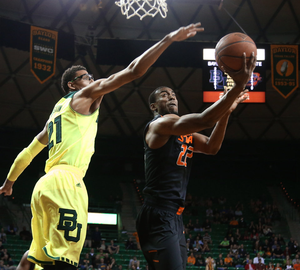 Photo - Oklahoma State guard Markel Brown (22), right, scores over Baylor center Isaiah Austin (21), left, in the first half of an NCAA college basketball game, Monday, Feb. 17, 2014, in Waco, Texas. (AP Photo/Waco Tribune Herald, Rod Aydelotte)