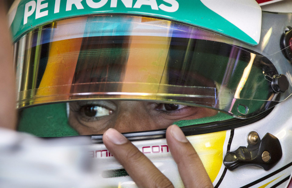 Photo - CORRECTS PHOTO CREDIT TO PAUL CHIASSON Mercedes driver Lewis Hamilton from Great Britain adjusts his helmet as he sits in his car during the third practice session at the Canadian Grand Prix Saturday, June 7, 2014 in Montreal.  (AP Photo/The Canadian Press, Paul Chiasson)