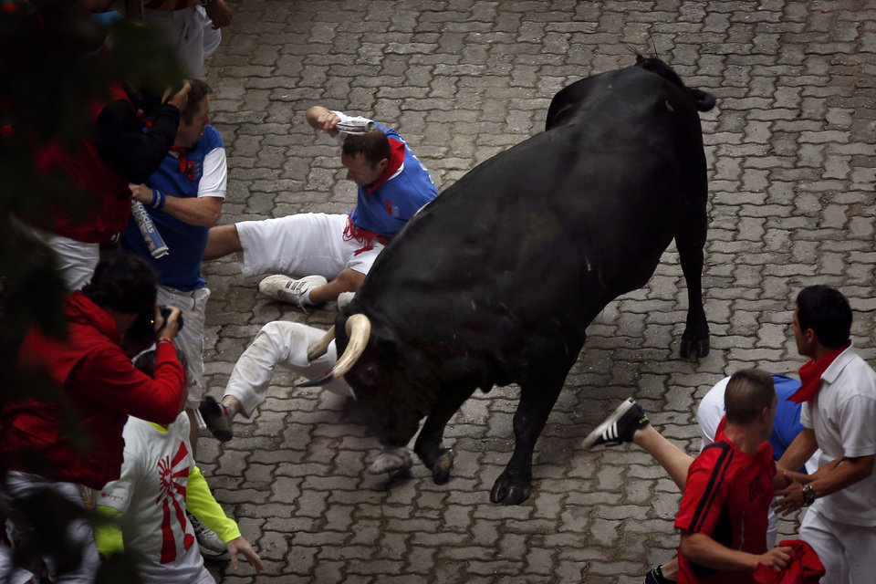 Photo - U.S. runner Bill Hillmann, 35, from Chicago is gored on his right leg by a Victoriano del Rio ranch fighting bull during the running of the bulls of the San Fermin festival, in Pamplona, Spain, Wednesday, July 9, 2014. Revelers from around the world arrive in Pamplona every year to take part on some of the eight days of the running of the bulls glorified by Ernest Hemingway's 1926 novel
