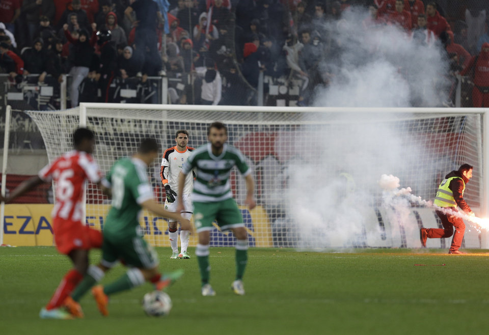 Photo - A security person removes a flare from  Panathinaikos' goalkeeper Stefanos Kapino's area during a Greek League soccer match against Olympiakos at Georgios Karaiskakis stadium, in Piraeus port, near Athens, on Sunday, March 2, 2014. Olympiakos' undefeated run is over after a 3-0 home defeat by Panathinaikos. Very little soccer was played in the last 12 minutes, as Olympiakos fans kept throwing flares and projectiles after they had a penalty awarded in their favor. (AP Photo/Thanassis Stavrakis)
