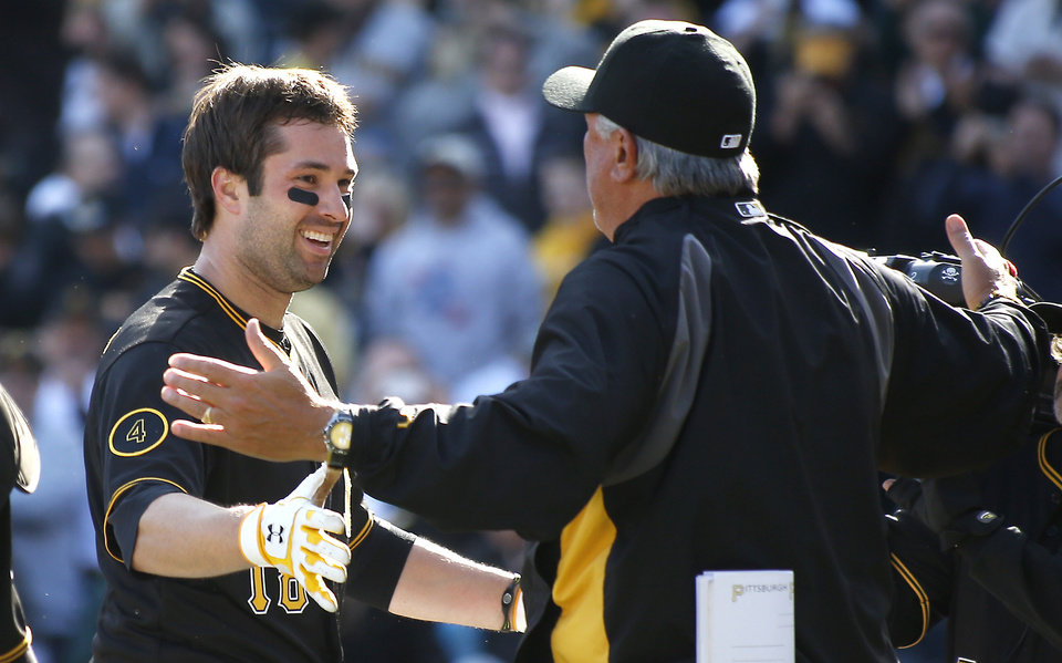 Photo - Pittsburgh Pirates' Neil Walker, left, is greeted by manager Clint Hurdle after hitting the game winning home run in the tenth inning on an opening day baseball game against the Chicago Cubs on Monday, March 31, 2014, in Pittsburgh. The Pirates won 1-0 in ten innings. (AP Photo/Keith Srakocic)