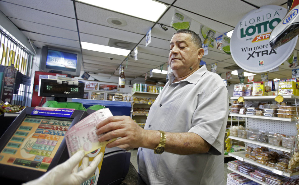 Remberto Gonzalez purchases Powerball lottery tickets at a local store in Hialeah, Fla., Tuesday, Aug. 6, 2013. On Tuesday, the Powerball jackpot reached $425 million for Wednesday\'s drawing. (AP Photo/Alan Diaz)