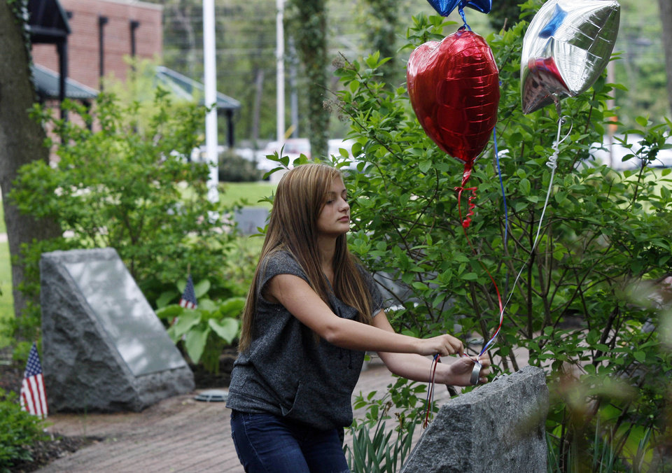 Photo - Fourteen-year-old Kristen Grazioso places balloons on a carved stone Monday, May 2, 2011, in Middletown, N.J., that  honors her father, who was killed in the attacks on the World Trade Center on Sept. 11, 2001. There are 37 stones in the garden representing those from Middletown who died in the attack. Word came late Sunday, May 1, 2011 the Osama Bin Laden has been killed. (AP Photo/Mel Evans)