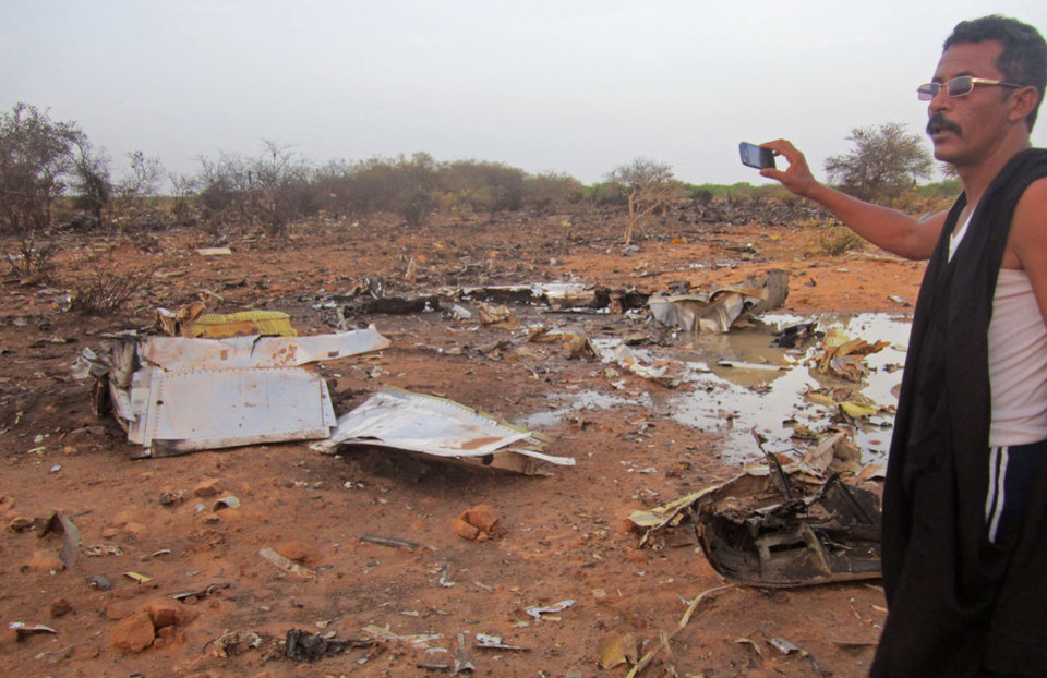 Photo - This photo provided on Friday, July 25, 2014,  by the Burkina Faso Military shows  a man at the site of the plane crash in Mali. French soldiers secured a black box from the Air Algerie wreckage site in a desolate region of restive northern Mali on Friday, the French president said. Terrorism hasn't been ruled out as a cause, although officials say the most likely reason for the catastrophe that killed all onboard is bad weather. At least 116 people were killed in Thursday's disaster, nearly half of whom were French. (AP Photo/Burkina Faso Military)