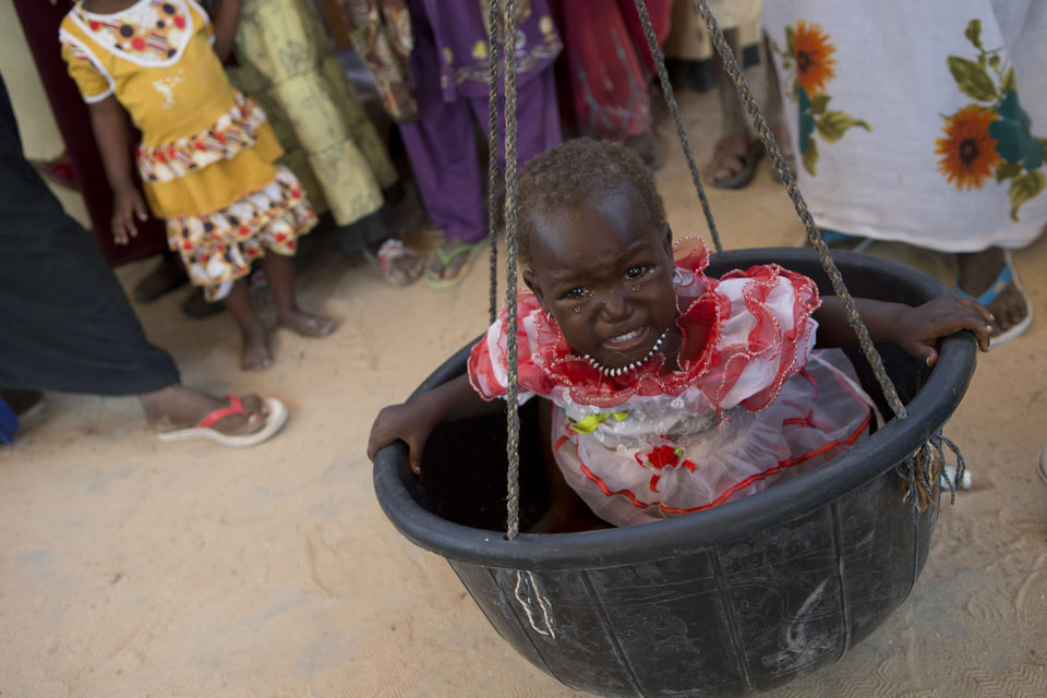 In this Nov. 4, 2012 photo, a little girl cries as she is weighed as part of a mobile nutrition clinic to examine local children and identify cases of underweight, stunted, or malnourished children, in Michemire, in the Mao region of Chad. A survey conducted in the county found that 51.9 percent of children are stunted, one of the highest rates in the world, according to a summary published by UNICEF. Stunting is the result of having either too few calories, too little variety, or both. (AP Photo/Rebecca Blackwell) ORG XMIT: NY877