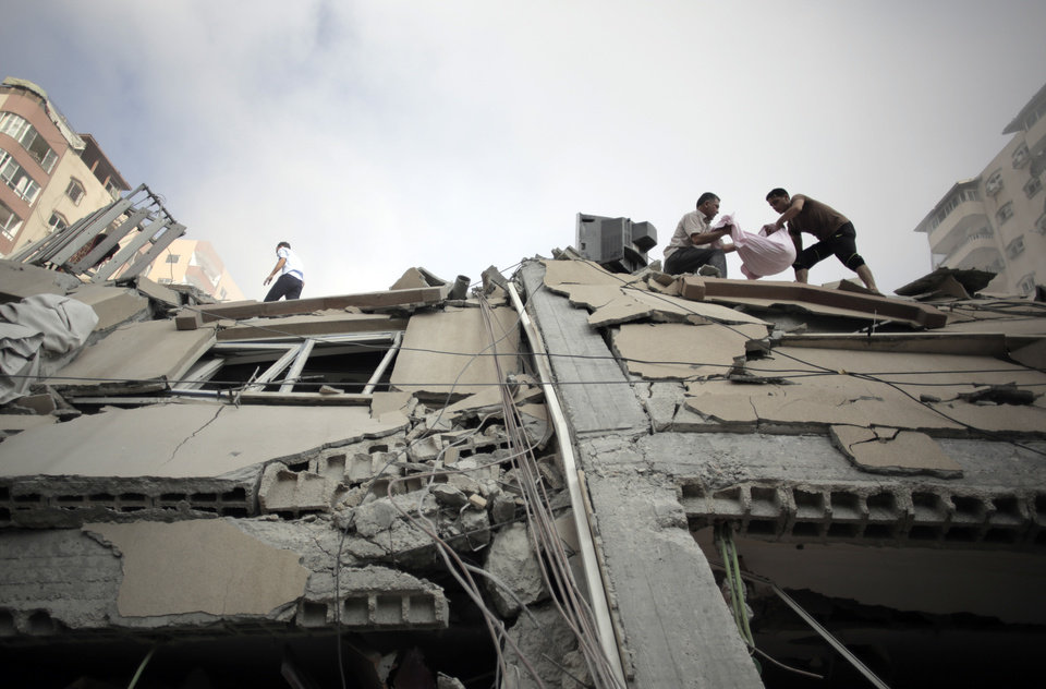 Photo - Palestinians inspect the rubble and salvage items from the Al-Zafer apartment tower following Israeli airstrikes Saturday that collapsed the 12-story building, in Gaza City, Sunday, Aug. 24, 2014. The army said the Gaza City apartment tower was targeted because a Hamas command center operated from there. The weekend strikes by Israel marked the first time large buildings were toppled signaling a new escalation in seven weeks of fighting with Hamas. (AP Photo/Khalil Hamra)